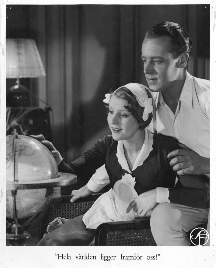 Huvudrollsinnehavarna i svenska versionen blickar på en jordglob från Vi som går köksvägen (1932)