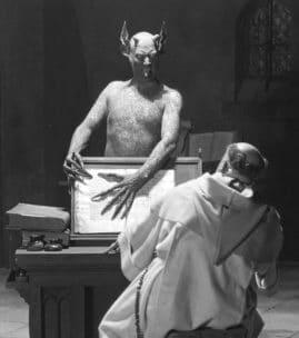 Bild ur filmen Häxan med regissören Benjamin Christensen som djävulen som skrämmer en munk